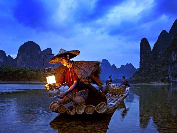 Pescador nocturno en el río Lijiang de China