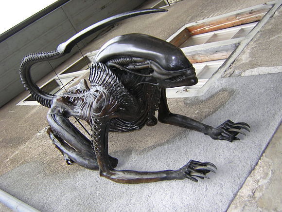 Alien trepando por la pared en la fachada del museo H.R. Ginger