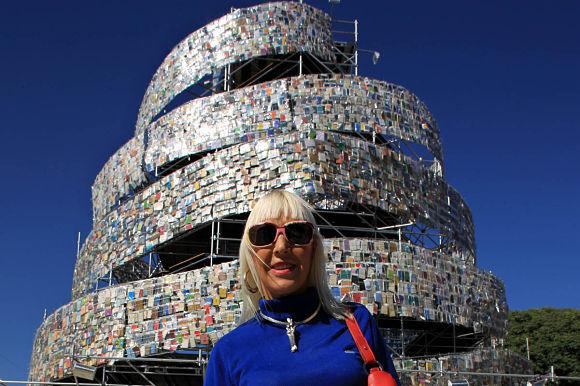 La artista Marta Mirujín posando con su particular Torre de Babel