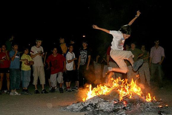 Fotografía de un joven saltando una hoguera para atraer a la buena suerte durante la Noche de San Juan