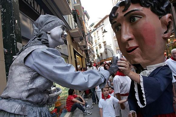 El cabezudo de la abuela recibiendo una manzana de una estatua en los Sanfermines