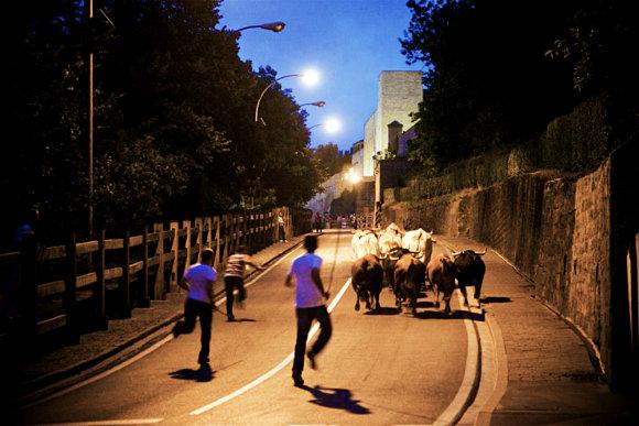 Los pastores corren detrás de los astados en el encierrillo de las Fiestas de San Fermín