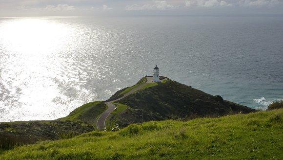 El faro Cape Reinga alumbrado por el sol, iluminando en mar de Tasmania