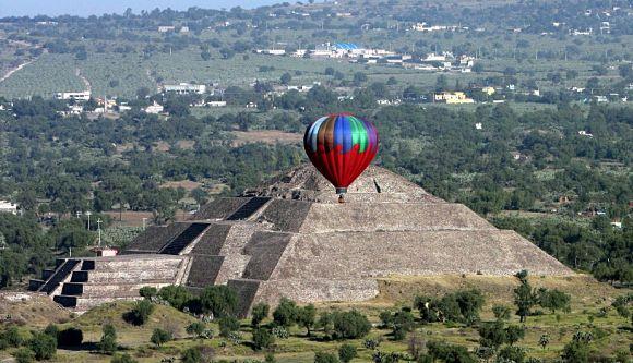 Imagen de la Pirámide del Sol de Teotihuacan con un globo aerostático surcando el cielo