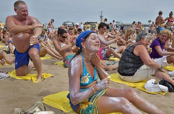 Personas echándose crema solar en la playa