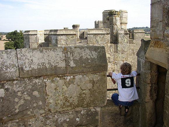 Niño observando el horizonte subido en las murallas del castillo de Bodiam