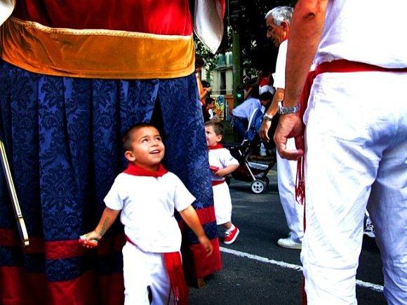 Un niño inocente sonríe abiertamente bajo las faldas de un gigante en los Sanfermines