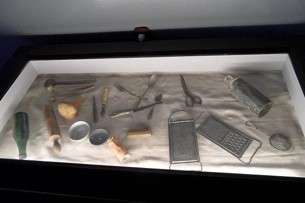 Imagen de una urna de cristal con utensilios de los prisioneros de Auschwitz